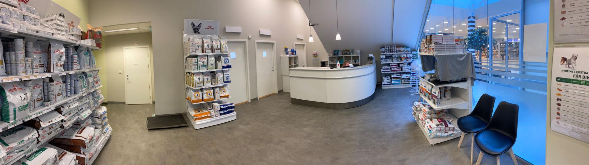 Resepsjonen hos Liertoppen Dyreklinikk. Hyller med dyremat og andre produkter, dører til konsultasjonsrom i bakkant.